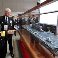Maritime Self-Defense Force Rear Adm. Tadatsune Nishiyama (left) shows a model of the Izumo helicopter destroyer to U.S. Navy Capt. James Dick during the MAST Asia 2015 defense trade show at the Pacifico Yokoyama convention center on Wednesday. | YOSHIAKI MIURA