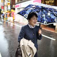 Hiromi Nakasaki, a software industry consultant who uprooted her life to look after her ailing mother, walks along a street in Tokyo last month. While Prime Minister Shinzo Abe promotes the idea that the workforce needs more women, the government has done little to lift the burden of their traditional obligation to care for the elderly. | BLOOMBERG