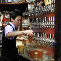 Beer necessities: A bartender pours glasses of craft beer at Bakusyu Club Popeye in Tokyo's Ryogoku neighborhood last weekend. | BLOOMBERG