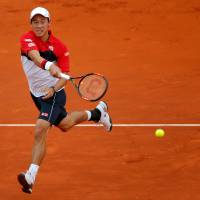 Pain in Spain: Kei Nishikori returns the ball to Andy Murray during their Madrid Open semifinal on Saturday. Murray won 6-3, 6-4. | AP