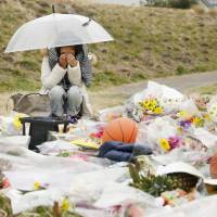 A woman cries on the banks of the Tama River in February in Kawasaki, where 13-year-old Ryota Uemura was fatally stabbed. | KYODO