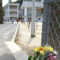 Flowers are left at the gate of an elementary school in Sasebo, Nagasaki Prefecture, in June 2004. | KYODO