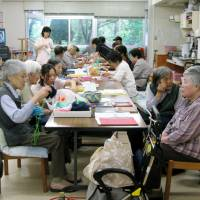 Elderly people sit at tables in a public hospital in Hiroshima. | KYODO