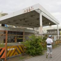 A man runs past an abandoned gas station in Izumisano, Osaka Prefecture. | KYODO