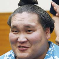 Always in style: Terunofuji has his hair retouched after winning the Summer Grand Sumo Tournament on Sunday.   KYODO