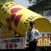 Not having it: A police officer stands guard in front of a protesters' float during this month's annual May Day rally in Tokyo. The government recently declared nuclear power to be the cheapest form of energy for the future, but critics don't agree. | REUTERS