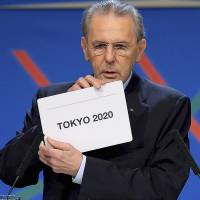 International Olympic Committee (IOC) President Jacques Rogge shows the name of the city of Tokyo elected to host the 2020 Summer Olympics during a session of the IOC in Buenos Aires, in September  2013.   | AFP-JIJI / POOL / FABRICE COFFRINI