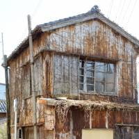 There goes the neighborhood: With trademark rust and overgrown with weeds, one of Japan's millions of akiya, or empty dwellings, stands — barely — in Nachikatsuura, Wakayama Prefecture. | KYODO