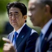 Brothers in arms: Prime Minister Shinzo Abe looks on as U.S. President Barack Obama speaks during a joint news conference in the Rose Garden at the White House on April 28. | BLOOMBERG