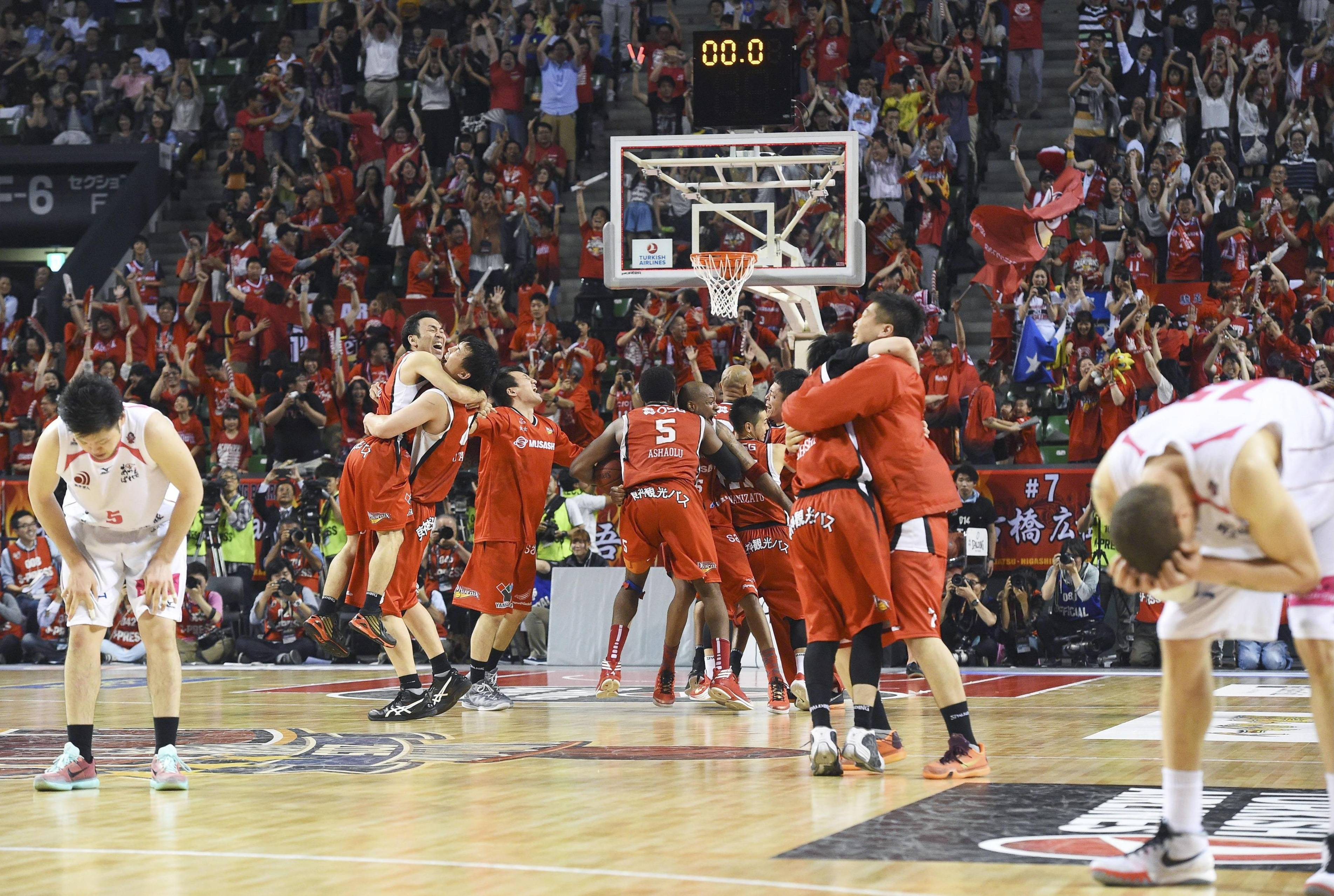 Third time's the charm: Hamamatsu Higashimikawa Phoenix players celebrate at the buzzer after beating the Akita Northern Happinets 71-69 to win the bj-league championship on Sunday. | KYODO