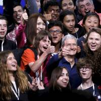 Apple CEO Tim Cook poses with scholarship winners following his keynote address at the Worldwide Developers Conference in San Francisco on Monday. | REUTERS