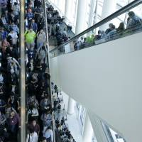 Apple Worldwide Developers Conference attendees ride escalators after a presentation in San Francisco on Monday. | AP