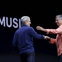 Apple CEO Tim Cook (left) greets senior vice president of internet services and software Eddy Cue during his keynote address on Monday at the Worldwide Developers Conference in San Francisco, California, | REUTERS