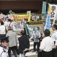 Antinuclear activists shout slogans as shareholders of Kansai Electric Power Co. head to a shareholders meeting Thursday in Kobe. | KYODO