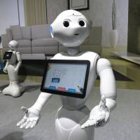 A Pepper robot shows off a photo journal entry it 'wrote' during a demonstration Thursday, when SoftBank Corp. announced that the humanoid robots will go on sale to the general public this weekend. | KAZUAKI NAGATA