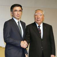 Suzuki Motor Corp. President Osamu Suzuki (right), the longest-serving leader of any major global automaker, cedes his title to his son, Toshihiro, during a news conference Tuesday in the city of Osaka. | KYODO