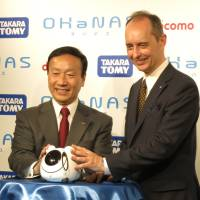 NTT Docomo Inc. President Kaoru Kato (left) and Tomy Co. COO H.G. Meij pose with Tomy's new communication robot Ohanas at a news conference Thursday to unveil the product. | KAZUAKI NAGATA