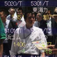 Pedestrians are reflected on a share prices board in Tokyo on Tuesday. Real wages rose in April for the first time in two years, although household spending contracted compared to a year earlier. | AFP-JIJI