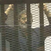 Mohammed Morsi, ousted as president, gestures in the defendants' cage at the Police Academy courthouse in Cairo on Tuesday, when the court confirmed his death sentence. | AP