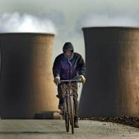 A cyclist battles the wind on a service road near a power plant operated by Datang International Power Generation Co. in Beijing in this 2004 file image. | BLOOMBERG