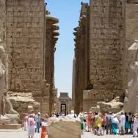 Tourists visit Karnak temple in Luxor, a town 700 km south of Cairo, on Thursday. The ancient temple was open as usual despite a foiled suicide and gun attack on the world-famous site that police said would have been a 'massacre.' Egyptian authorities are worried that Islamic militants are targeting the nation's tourist sites, the nation's economic lifeline. | AFP-JIJI