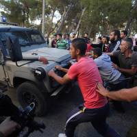 Israeli soldiers attempt to breakup a sit-in by Palestinians in the village of Kafr Malik, northeast of Ramallah on Sunday after clashes that resulted in the death of 21-year-old Palestinian Abdallah Ghanayem. An army spokesman told AFP that the Palestinian had died after he threw an incendiary device at a jeep and the vehicle overturned on him. Palestinian security sources said Israeli soldiers killed Ghanayem by hitting him with their jeep during clashes near Ramallah in the occupied West Bank. | AFP-JIJI