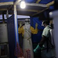 An MSF Ebola heath worker is sprayed last November as he leaves the contaminated zone at the Ebola treatment center in Gueckedou, Guinea. | FILE / JEROME DELAY / AP