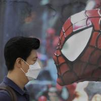 A South Korean man wearing a mask as a precaution against the Middle East respiratory syndrome walks by a Spider-Man poster advertising a musical for children in Seoul on Wednesday.   AP