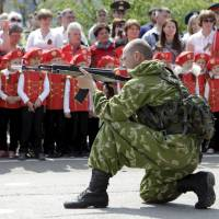 A Russian paratrooper performs for children during the so-called parade of children's troops in the Russian city of Rostov-on-Don on May 14. | REUTERS