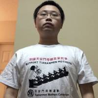 University of Georgia graduate student Gu Yi poses in a T-shirt reading 'Support Tiananmen Mothers,' at home in Athens, Georgia. | AP