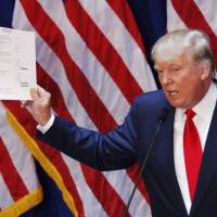 Real estate mogul Donald Trump, 69, displays his financial statement during his announcement that he will run for the 2016 presidential election at the Trump Tower in New York on Tuesday. Trump, one of America's most flamboyant and outspoken billionaires, threw his hat into the race promising to make America great again. | AFP-JIJI