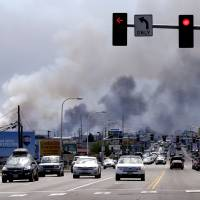 Smoke from several warehouses on fire, thought to have been sparked by embers from a wildfire that hit homes on a nearby hillside, fills the sky Monday in Wenatchee, Washington. The wildfires hit parts of central and eastern Washington over the weekend as the state is struggling with a severe drought, destroying dozens of structures and forcing hundreds to flee. | AP