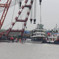 Rescuers standing Thursday on the overturned hull of the Eastern Star carry the body of a victim of the cruise ship's capsizing in Jianli, central China's Hubei province, before a giant floating crane begins work to right the vessel. Relatives of more than 400 people believed trapped inside the ship gathered at the disaster site as rescuers breached the hull in a last-ditch search for the missing. | AFP-JIJI
