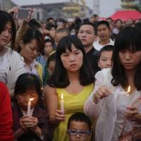 Local residents take part in a candlelight vigil to pay their respects to victims of the sunken ship Eastern Star in Jianli, China's Hubei province, on Thursday. | AFP-JIJI