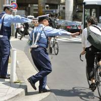 Police stop a cyclist who ignored a traffic light on Monday in Tokyo's Minato Ward. | KYODO