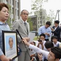 Holding a portrait of her late husband, Eiko Isozaki speaks to reporters Tuesday outside the Fukushima District Court. The court ruled that his suicide in July 2011 was linked to living as an evacuee and awarded her ¥27 million in damages. | KYODO