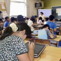 Students at Fujinoki Elementary School in Hiroshima use tablet computers in class last July. The government is considering introducing digital textbooks as more classrooms become digitized. | KYODO