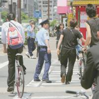 Police officers in Osaka urge cyclists June 1 to heed traffic rules after the revised Road Traffic Law took effect that day. | KYODO
