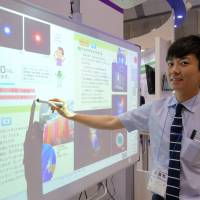 An employee of a textbook publisher Tokyo Shoseki Co. shows a digital textbook equipped with such features as a marker and a magnifier at the Educational IT Solutions Expo held May 20 in Tokyo. | SHUSUKE MURAI