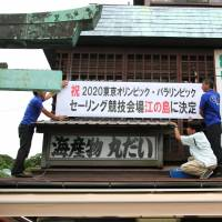 Workers hang a banner Tuesday on a building on Enoshima off Fujisawa, Kanagawa Prefecture, celebrating the island's choice to host the sailing events in the 2020 Tokyo Olympics. | KYODO