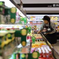 A store worker checks products at an Aeon Co. supermarket in Tokyo in 2013. Products bearing new explanatory food labels will hit stores nationwide this week. | BLOOMBERG