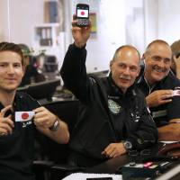 Bertrand Piccard (center), the initiator, chairman and one of the pilots of the Solar Impulse 2, holds up a smartphone bearing a Japanese flag, flanked by Deniz Borschberg, whose father, Andre, is flying the aircraft, and Solar Impulse mission director Raymond Clerc (right), at Mission Control Center in Monaco, after the plane landed safely Monday night in Nagoya. | AFP-JIJI