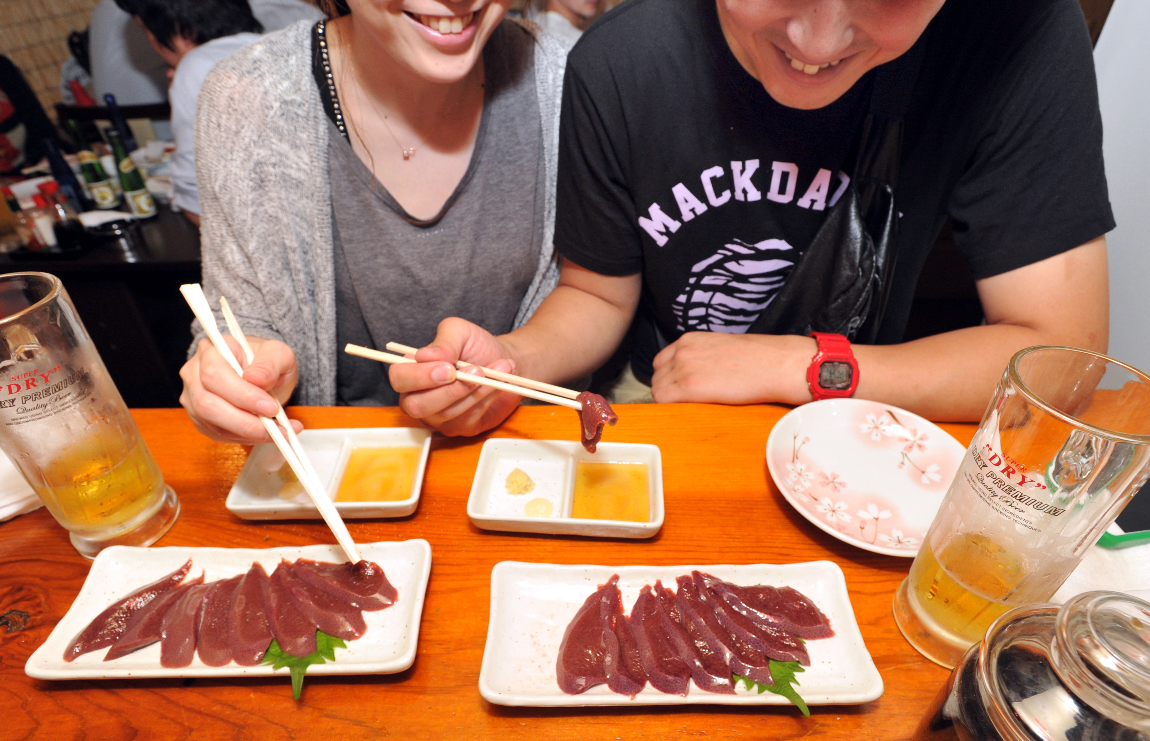 Customers at Aji no Isohei, a traditional Japanese pub in Tokyo's Oimachi district, eat raw pork liver Thursday evening before a new regulation banning it took effect the following day.  | YOSHIAKI MIURA