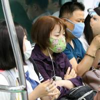 People wear masks on a subway in Seoul on Wednesday, amid an outbreak of Middle East Respiratory Syndrome. | KYODO