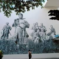 Toshiro Mifune (front) in Akira Kurosawa's 'Seven Samurai' is depicted in this design painted on the front to Toho Studio. The claw of a Godzilla statue can be seen at the right. Both classic movies were released in 1954.   KYODO