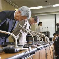 Japan Pension Service President Toichiro Mizushima (left) apologizes for the recent massive data breach during a news conference Monday at the welfare ministry.   KYODO