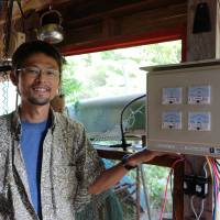 Shuntaro Suzuki, who teaches people how to make their own solar-power battery packs at Fujino Power, stands beside a control box in his house that he made to test out new kinds of electrical circuits. | REBUILD JAPAN INITIATIVE FOUNDATION