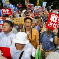Protesters hold banners outside the Diet building during a rally in Tokyo on Sunday. The protesters gathered to oppose a set of controversial bills intended to expand Japan's defense role at home and abroad. | AP