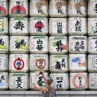 A tourist takes a photograph of a display of sake barrels at Meiji Shrine in Tokyo on May 6. The government plans to create a smartphone app that can scan sake labels to show related information in Japanese and English. | BLOOMBERG