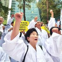 South Korean family members of victims of World War II chant slogans outside the Japanese Embassy in Seoul on Monday during an anti-Japan rally. | AFP-JIJI